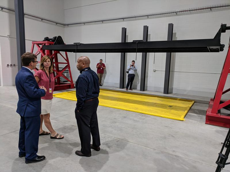 Director of Crash Test Operations Jerry Goupil explains the use of a rotisserie-like device in testing for fuel leaks after crash tests to New York State Assembly Speaker Carl Heastie and Assembly Member Monica Wallace