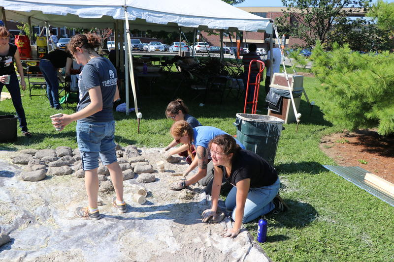 Students fashion bricks out of straw, sand, and clay for the base of an Iron Age smelting furnace during Buffalo State College's 'Days of Fire' event hosted by the Garman Art Conservation Department.