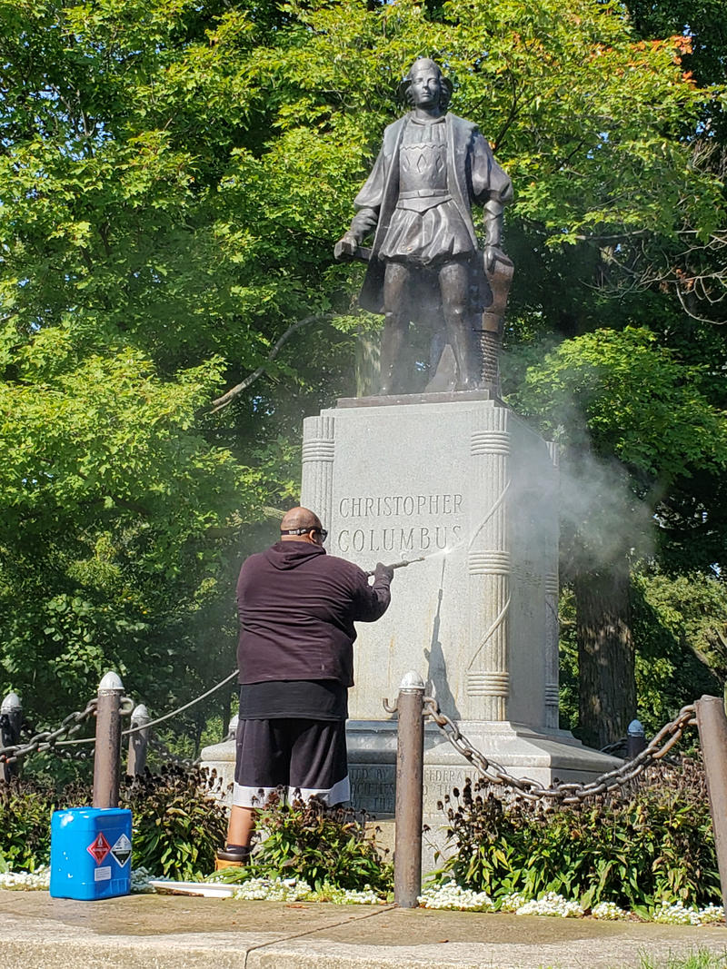 City workers clean paint off Christopher Columbus statue