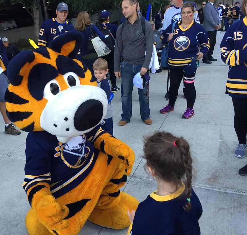 Buffalo Sabres mascot Sabretooth mingles with a young fan outside KeyBank Center Thursday evening.