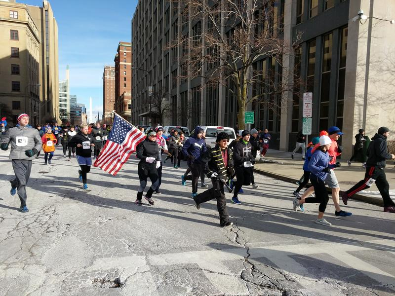 Runners in costume and carrying the American flag round the corner of Delaware Avenue onto Church Street - the southernmost point of the Turkey Trot route.
