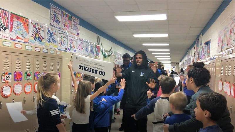 UB Bulls players high-five Dodge Elementary students.