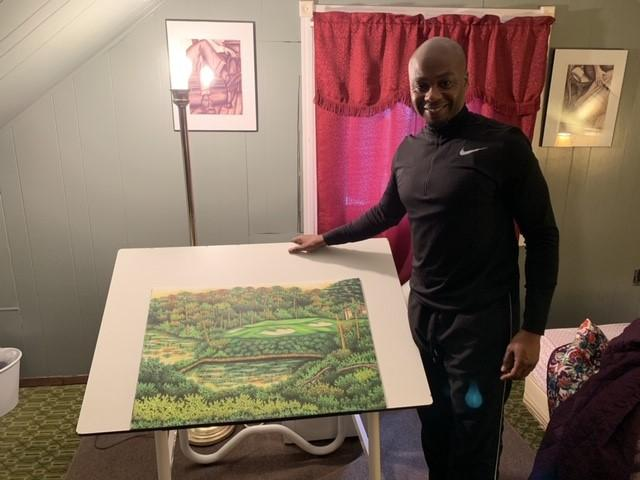 Valentino Dixon standing next to his art in his room