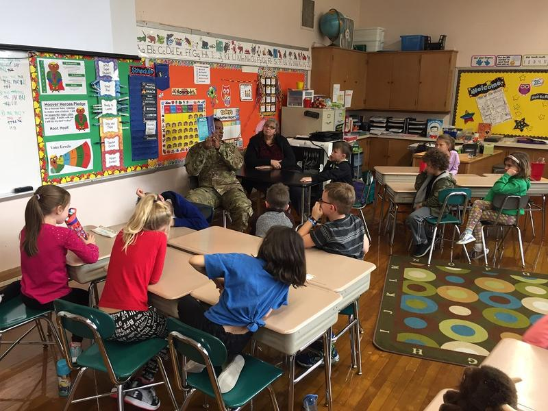 US Air Force Staff Sergeant Daniel Smith reads a book about drones to Mrs. Wilson's class in Hoover Elementary School, as part of the school's Veterans Day Celebration Thursday.