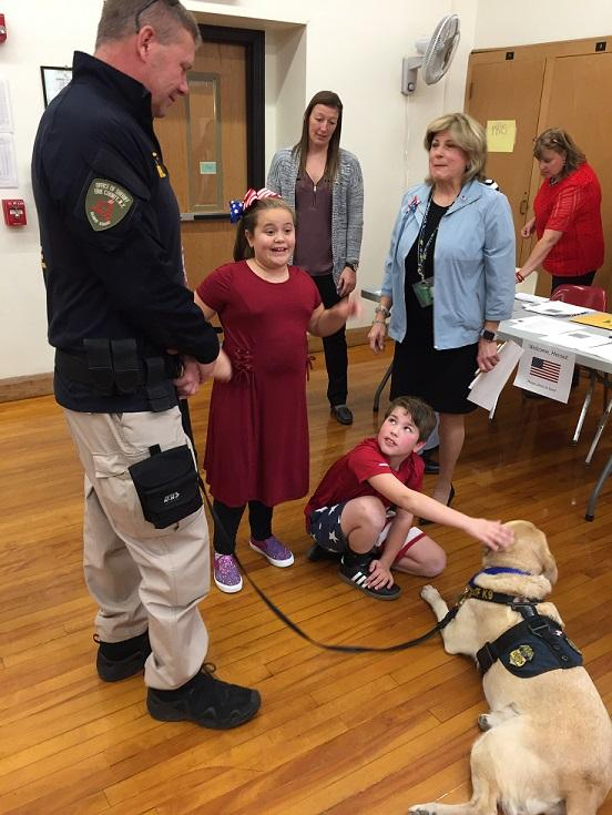 Students who served as escorts for their special guests Thursday get up close with a K9 officer with the Bureau of Alcohol, Tobacco & Firearms. In addition to military, members of first response agencies such as police, fire and ATF were also present.