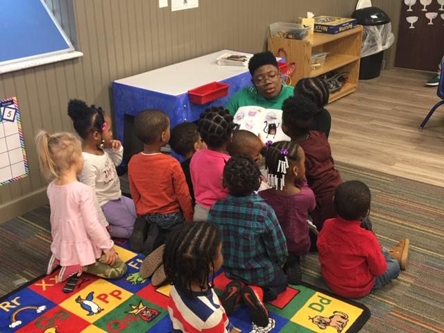 Three year olds gathered around their teacher inside a brand new classroom to listen to hear read Splat the Cat.