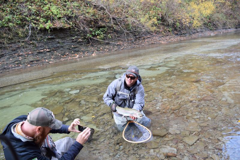 Patrick Robinson takes a picture of Ed Hays and his fresh catch before they release it back into Elk Creek