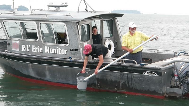 Dave Spangler takes a water sample from Lake Erie