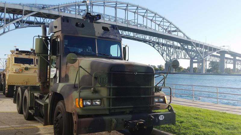 Vehicles wait under Blue Water Bridge for test