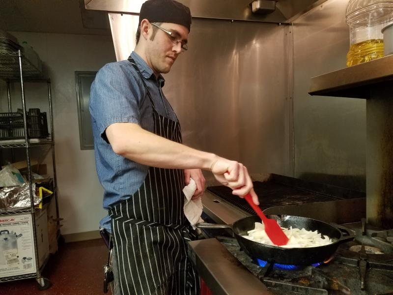 Chef Paul Vugteveen caramelizes some onions for a recipe at Sprout—a non-profit in Battle Creek that focuses on food access. Vugteveen uses garlic mustard in his cooking. He says he'll often make it into a pistou—a lot like pesto.