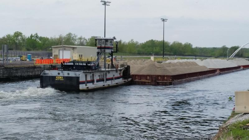 Tug boat pushes barge past electric barrier that helps to keep Asian carp out of Lake Michigan.