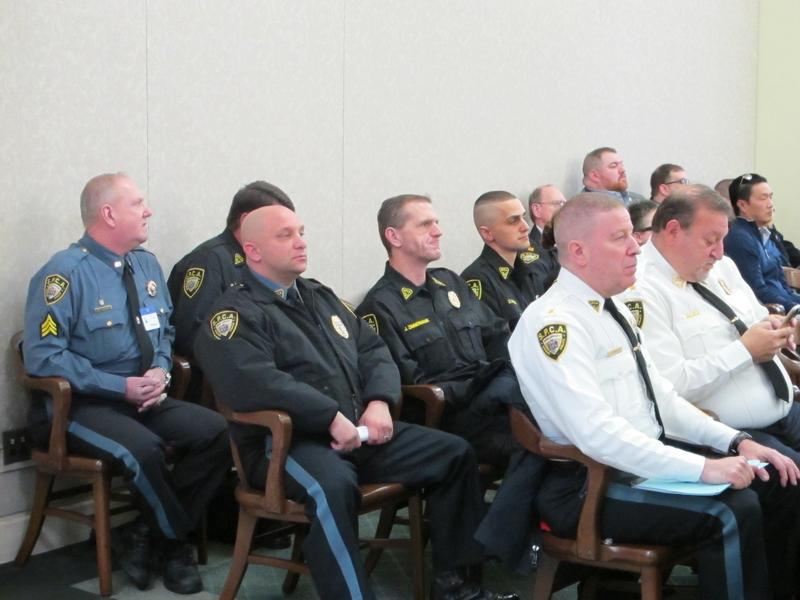 SPCA officers listen to testimony at legislative hearing.