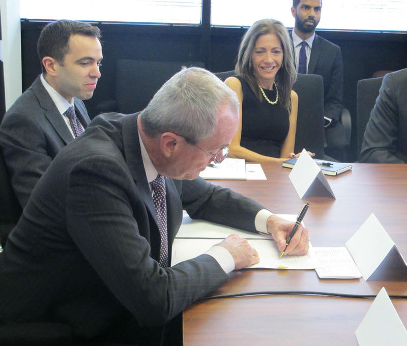 Murphy signs the executive order at a meeting of his cabinet.