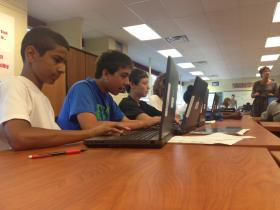 Eighth-grader Malique Tai and his group get together to work on a project.
