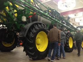 Young men check out John Deere's newest model of self-propelled sprayer.