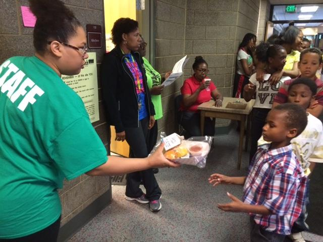 A staff member at Weisser Community Center hands a boy his lunch.