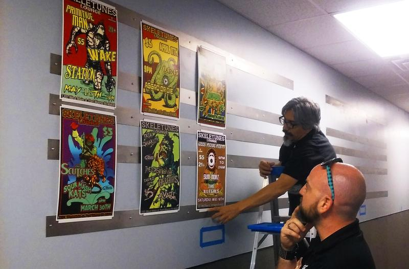 ART @ GC project coordinator, Jay Carroll (on ladder) with co-worker, Scott, hanging the upcoming show's display of Skeletune posters by Matthew Brown in the new gallery space.
