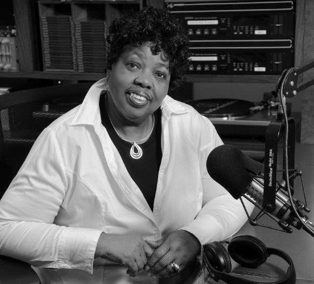 "Dee McKinley, volunteer host of WBOI's Sunday Morning ""Gospel Flight"" for over 30 years, behind the mic and ready for action in the WBOI air studio."