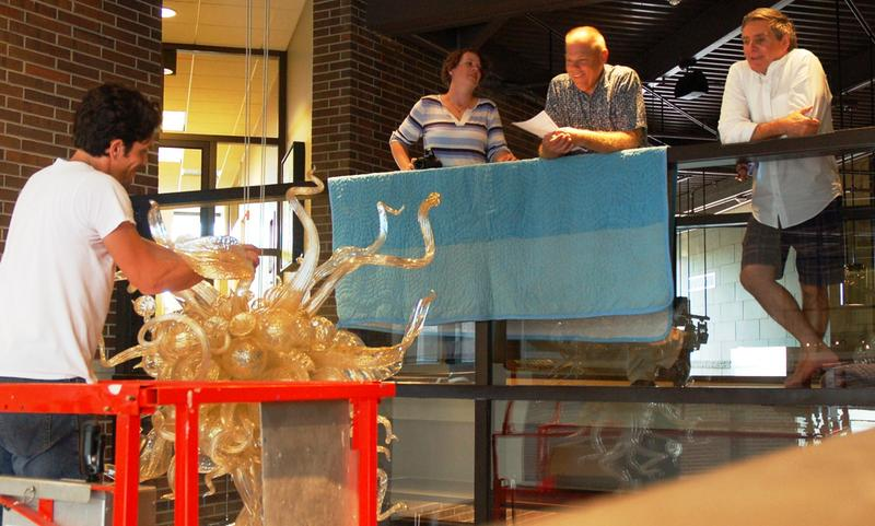 """Glass artist, Jacob Stout, on left, in installation mode with Chihuly's """"Lily Gold Chandelier"""" in the FWMoA while Charles Shepard (on far right) and museum staff observe."""