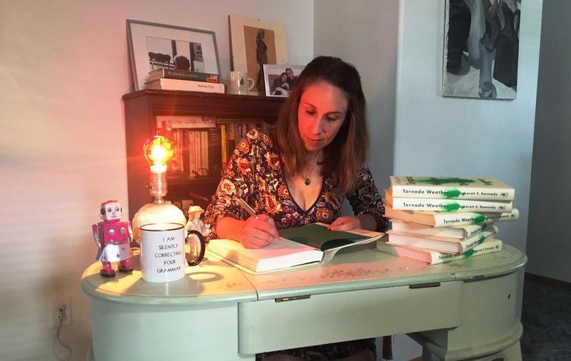 "Deborah Kennedy, in her home office, getting a jump on  book tour signing duties, for her 1st novel, ""Tornado Weather."""