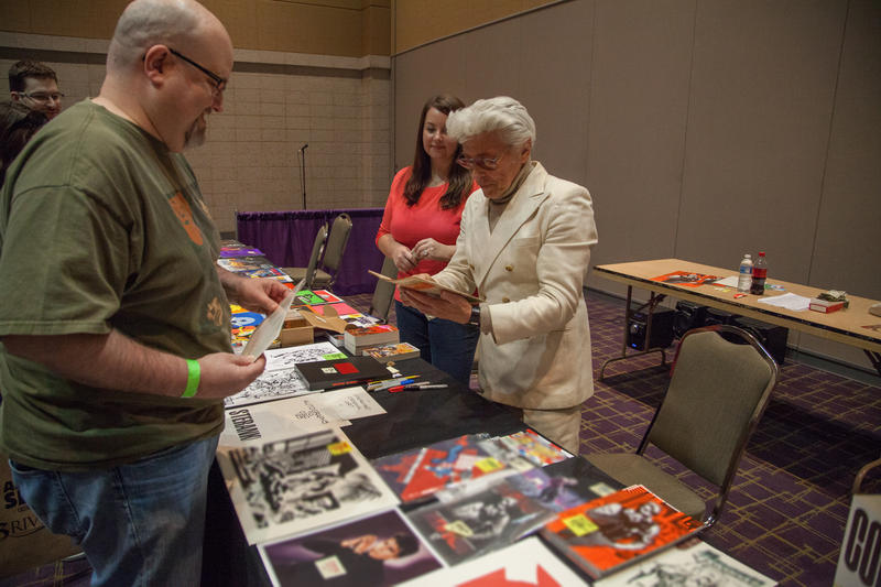 Comic book writer, artist, and publisher Jim Steranko (right) greets fans while con organizer Ashley Motia (center) looks on.