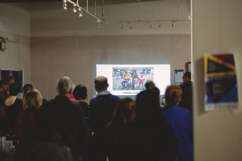 A crowd looks at pictures of refugees resettled in the US.