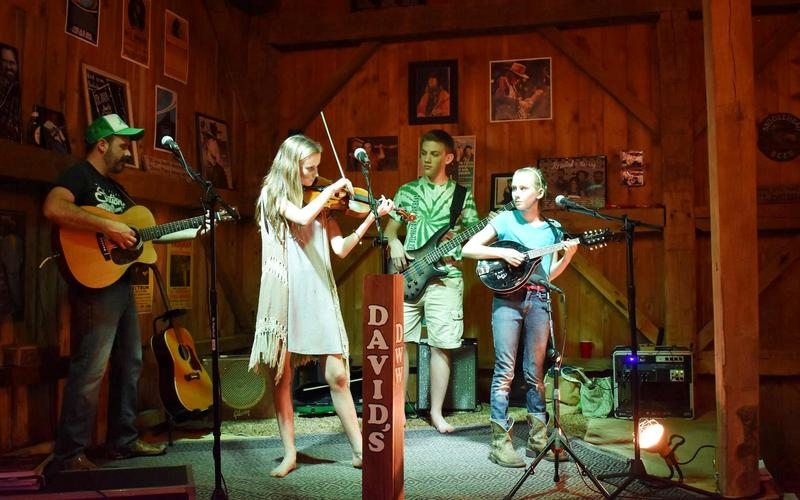 The St. Johns, and 4th band member, Paul, their cellist and bass player, on stage in the family barn.