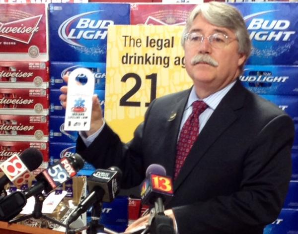 Indiana Attorney General Greg Zoeller poses with a tag promoting the state's Lifeline law, which gives legal immunity to minors seeking medical attention for other drunk minors.