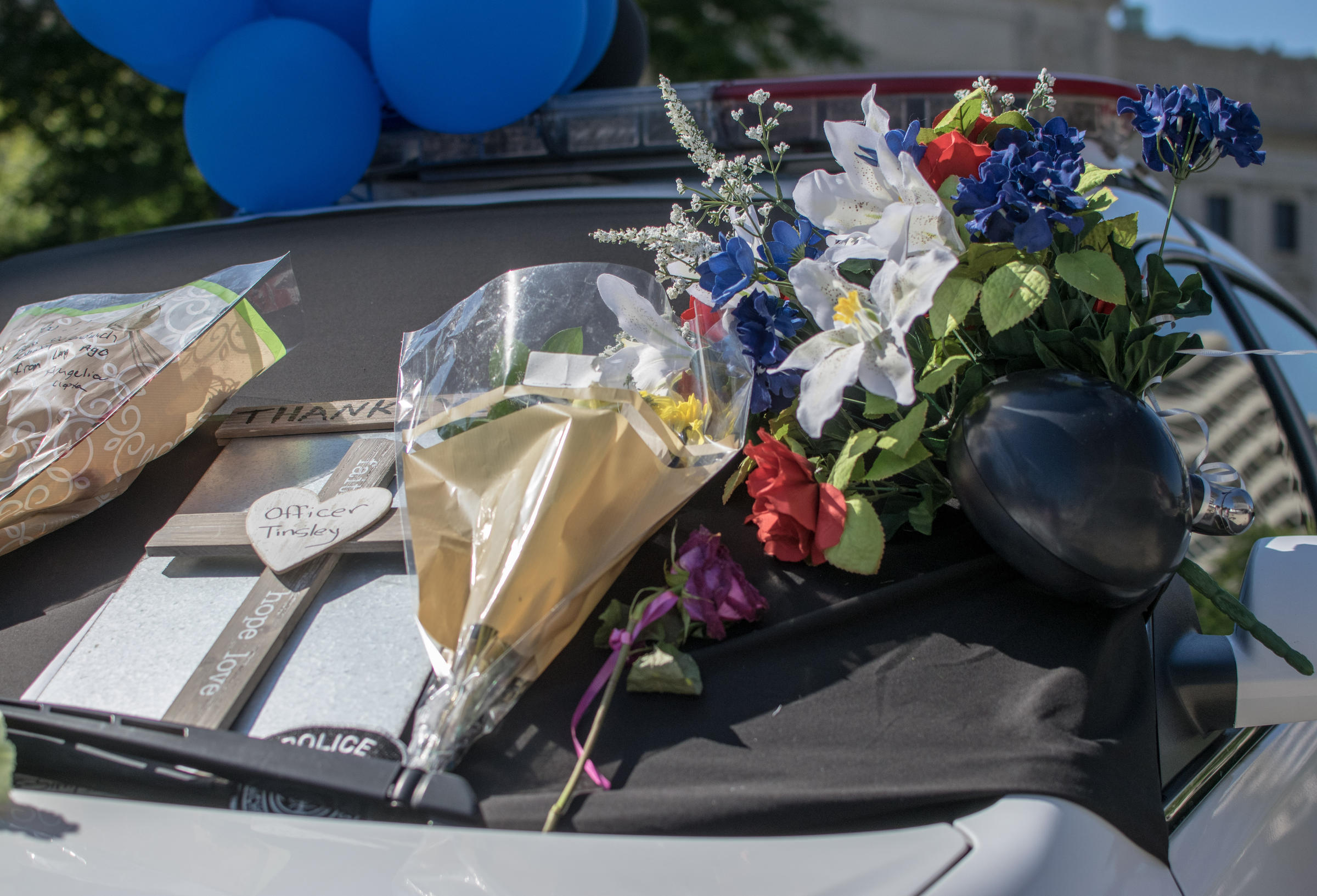 Officers funeral services set northeast indiana public radio flowers and notes adorn fwpd officer david tinsleys squad car as it sits outside the allen county courthouse as a public memorial to the officer izmirmasajfo
