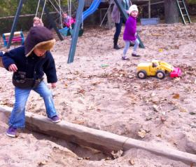exploring a sandy playground and swings