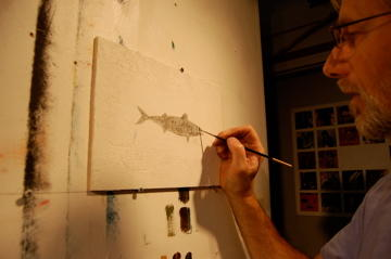King painting the mackerel he burned, with its ashes.