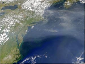 A satellite image shows a large plume of aerosol moving eastward over the North Atlantic Ocean.