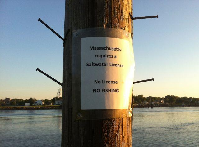 "Sign posted along the Cape Cod Canal: ""No License, NO FISHING."" This is just the third year that Massachusetts has required a Recreational Saltwater Fishing Permit."