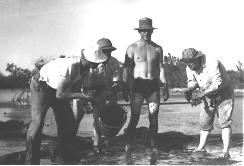 Bumpus (bare torso) and colleagues in mud, 1938