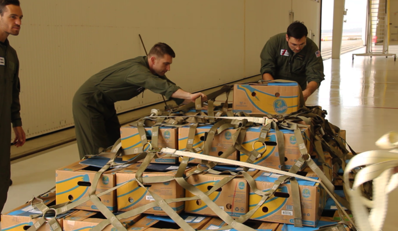 Two Coast Guard personnel secure the boxes of turtles for their flight.