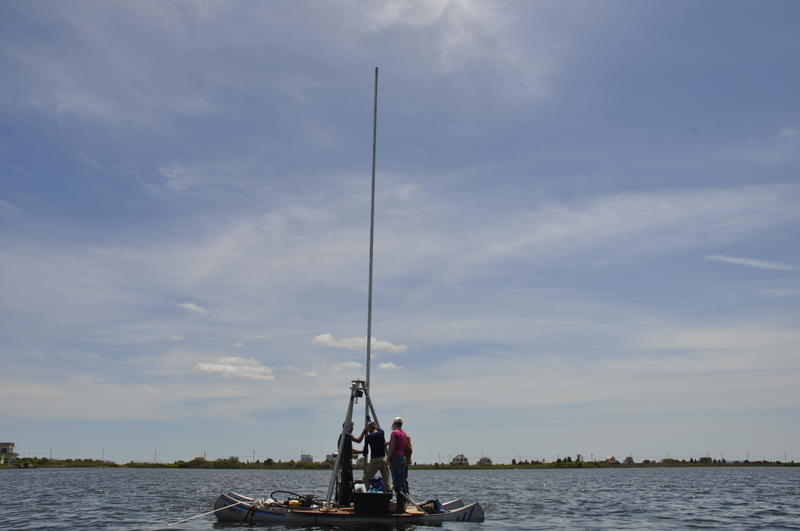 Scientists collect a sediment core from Salt Pond in Falmouth, MA.