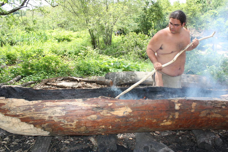 Wampanoag Indians at Plimoth Plantation burn and scrape out mishoon canoes with the same method Native Americans used centuries ago.