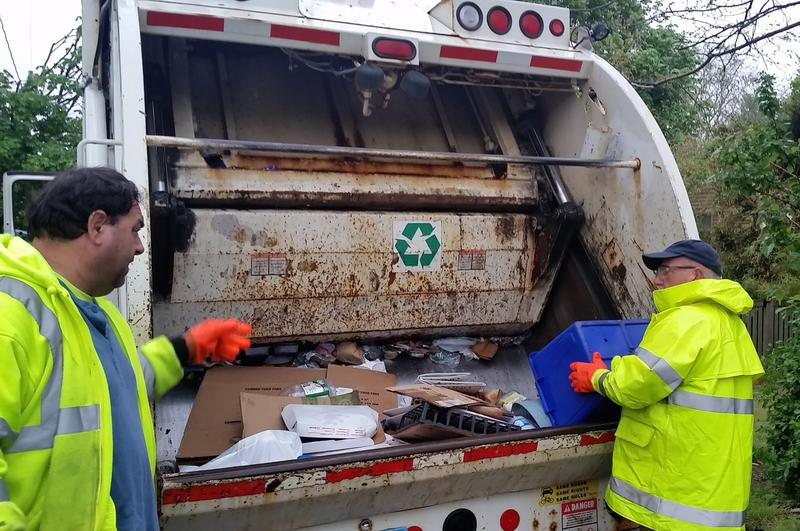 Provincetown DPW's Chris Roderick explains how the truck works while Don Beauregard picks up recyclables.
