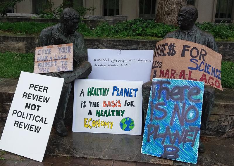 Statues supporting signs at the March for Science in Washington, D.C.