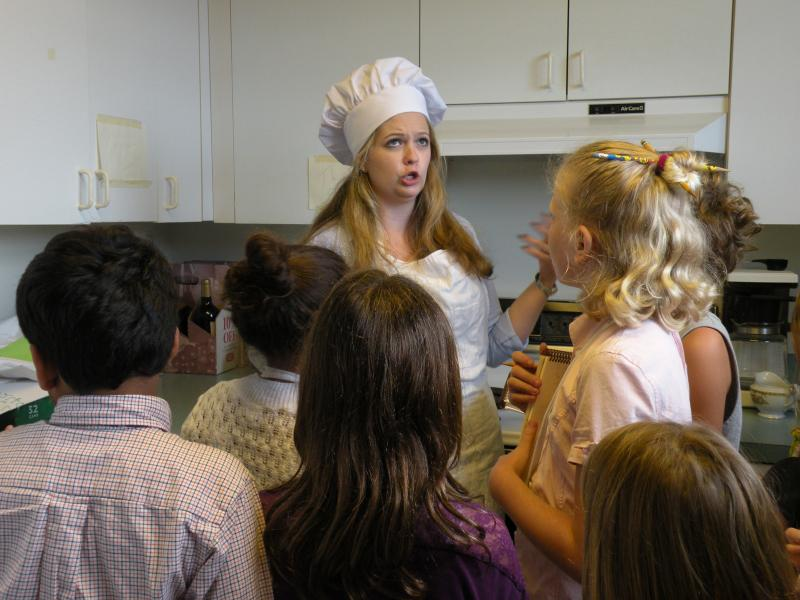 Campers interrogate Miss Epicure, the cook, in the Thurber Center kitchen.