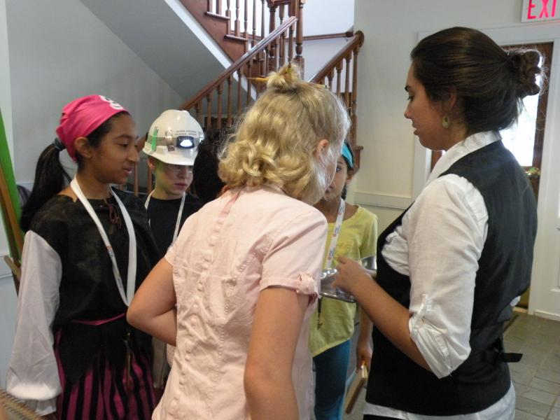 In the hall, campers accost the Butler on her way to deliver more tea.