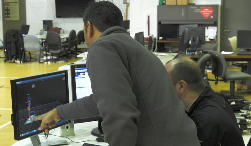 Ajit Chaudhari, PhD (left) and Mike McNally observe a simulation of a runner in a laboratory at The Ohio State University Wexner Medical Center as motion capture technology records how each bone and joint are affected with every stride.