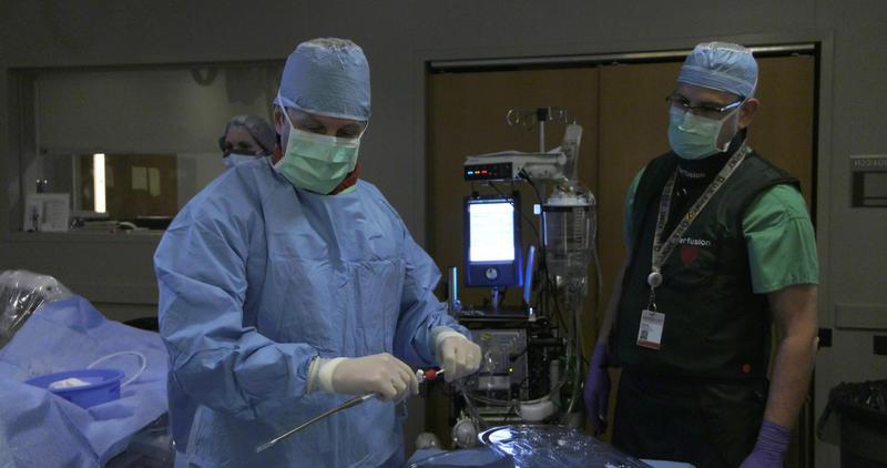 Dr. Ernest Mazzaferri (left) prepares a heart catheter for a cardiac arrest patient.