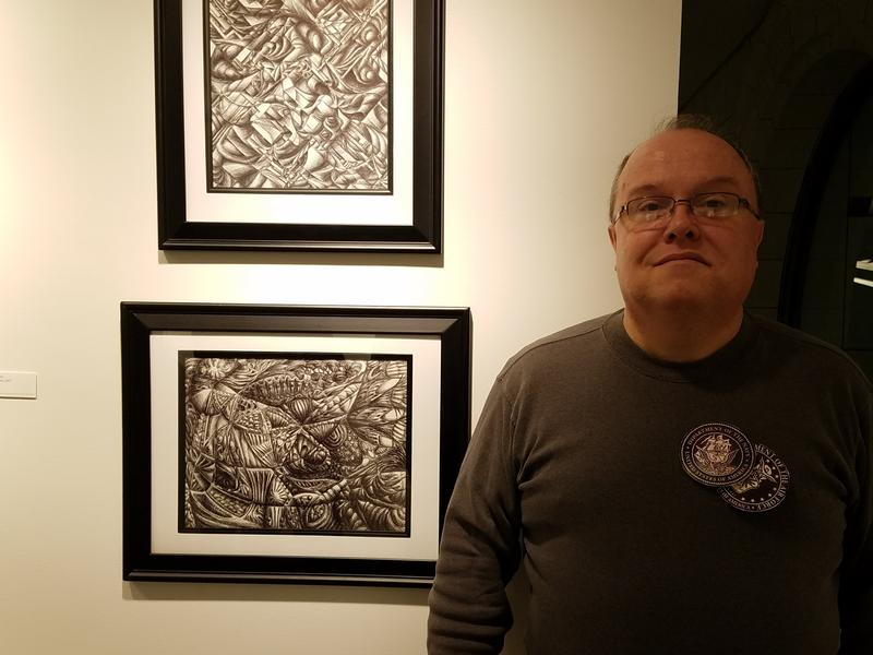 Veteran Patrick Paquin with a couple of his abstract art pieces
