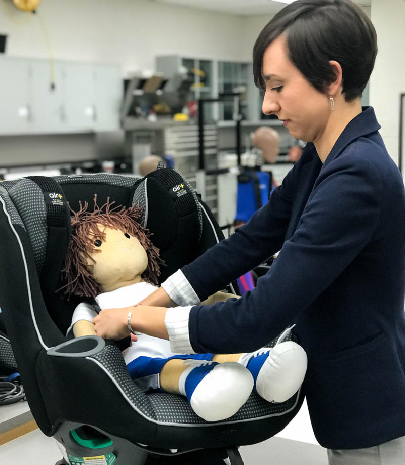 Julie Mansfield straps a doll into a car seat. Rear-facing car seats are known to protect children in front and side impact crashes, but are rarely discussed in terms of rear-impact collisions.