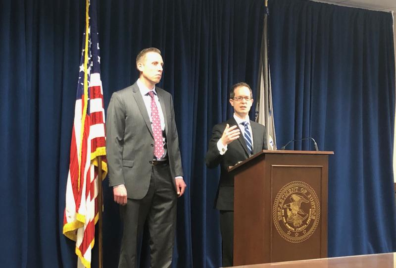 U.S. Attorney Benjamin Glassman speaking at the podium with IRS Criminal Investigation special agent Ryan Korner.