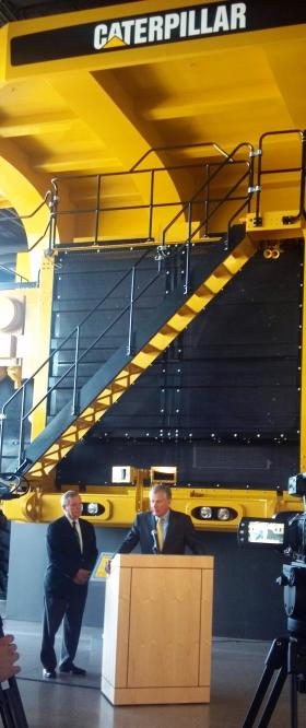 Sen. Dick Durbin (D-IL) and Caterpillar CEO Doug Oberhelman speak to reporters in-front of the replica 777D Mining Truck  that serves as the Caterpillar Visitors Center Theater.