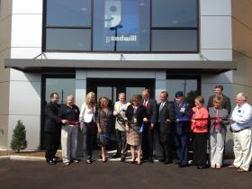 Ribbon cutting outside Goodwill Commons on War Memorial Drive Monday.