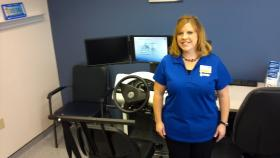 IPMR occupational therapist Sara Stomberg stands in front of the new driving simulator machine.