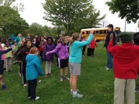 Students do a warm-up exercise before walking their last mile of the year.